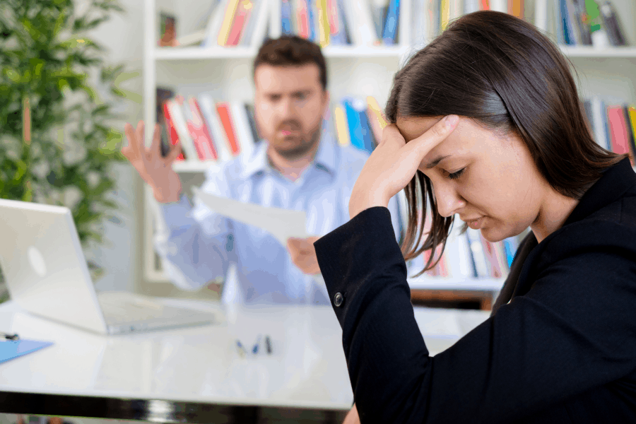 woman feeling sad in front of bad boss