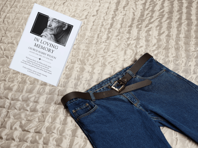 Jeans on a bed next to funeral program